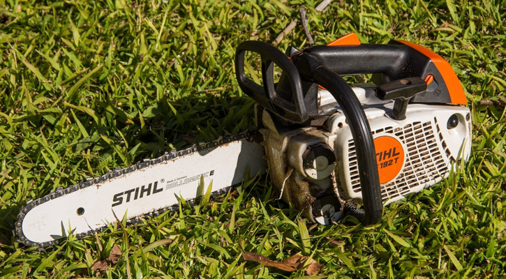Chainsaw laying in the grass waiting to be measured