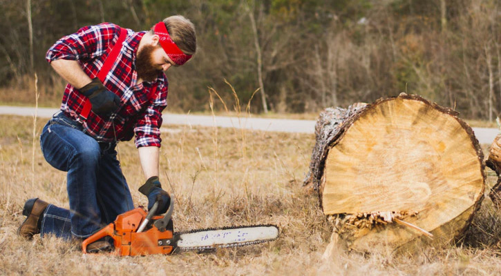 Lumberjack starting a chainsaw